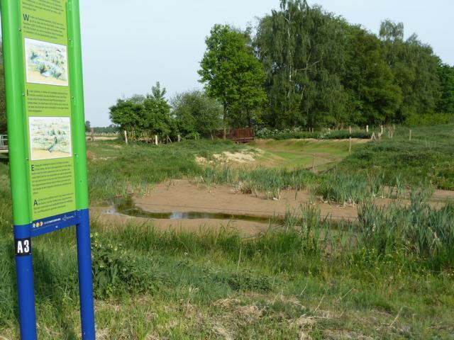 """Das Bachbett wurde erneut mit einer Wwasserhemmenden Lage ausgekleidet, der Krümelbach bei Niederbusch in sein früheres Kanalbett abgeleitet; im Vordergrund sioeht man ihn bei Eintritt in den Natuur- und Landschaftspark auh Höhe des """"heringshofs""""."""