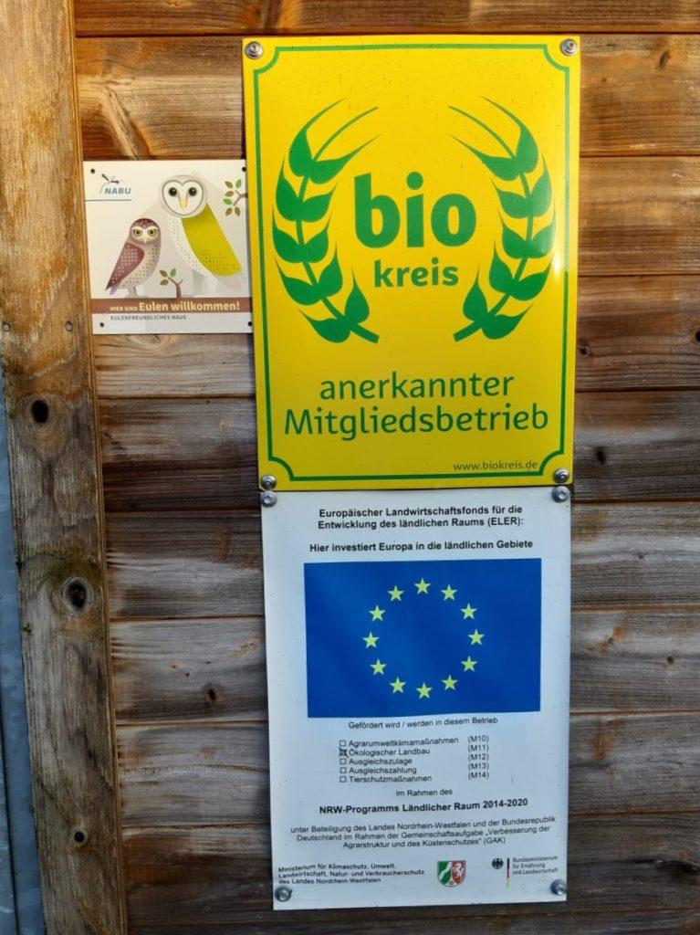 Die bunte NABU Plakette mit den Eulen-abbildungenveranschaulicht die naturnahe Bewirtschaftungsform auf dem Kollweider Hof in Breberen.